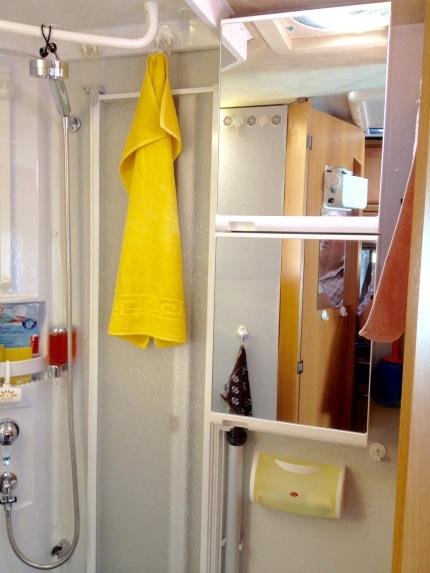 Rechts neben der Dusche: Übereonander montierte verspiegelte Kunststoffschränkchen